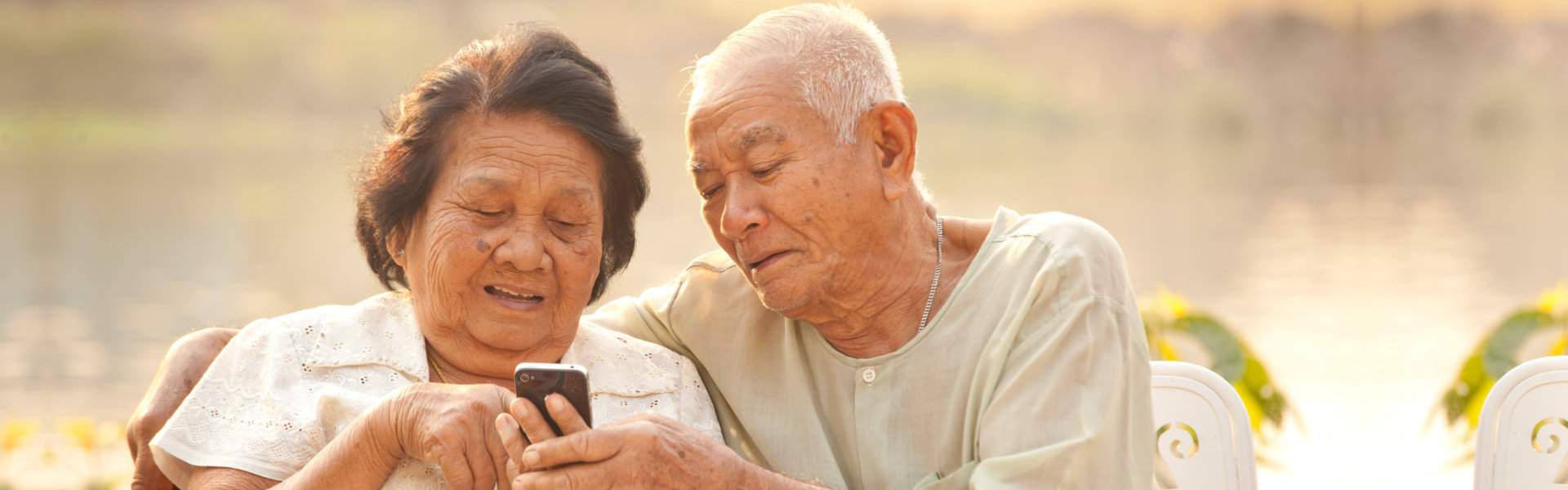 old woman holding a smartphone together with an old man